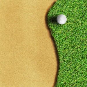 Golf ball in grass next to sand